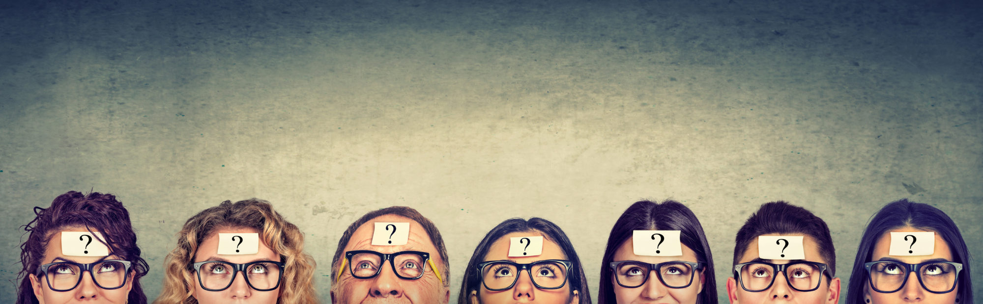 Multiethnic group of thinking people in glasses with question mark looking up